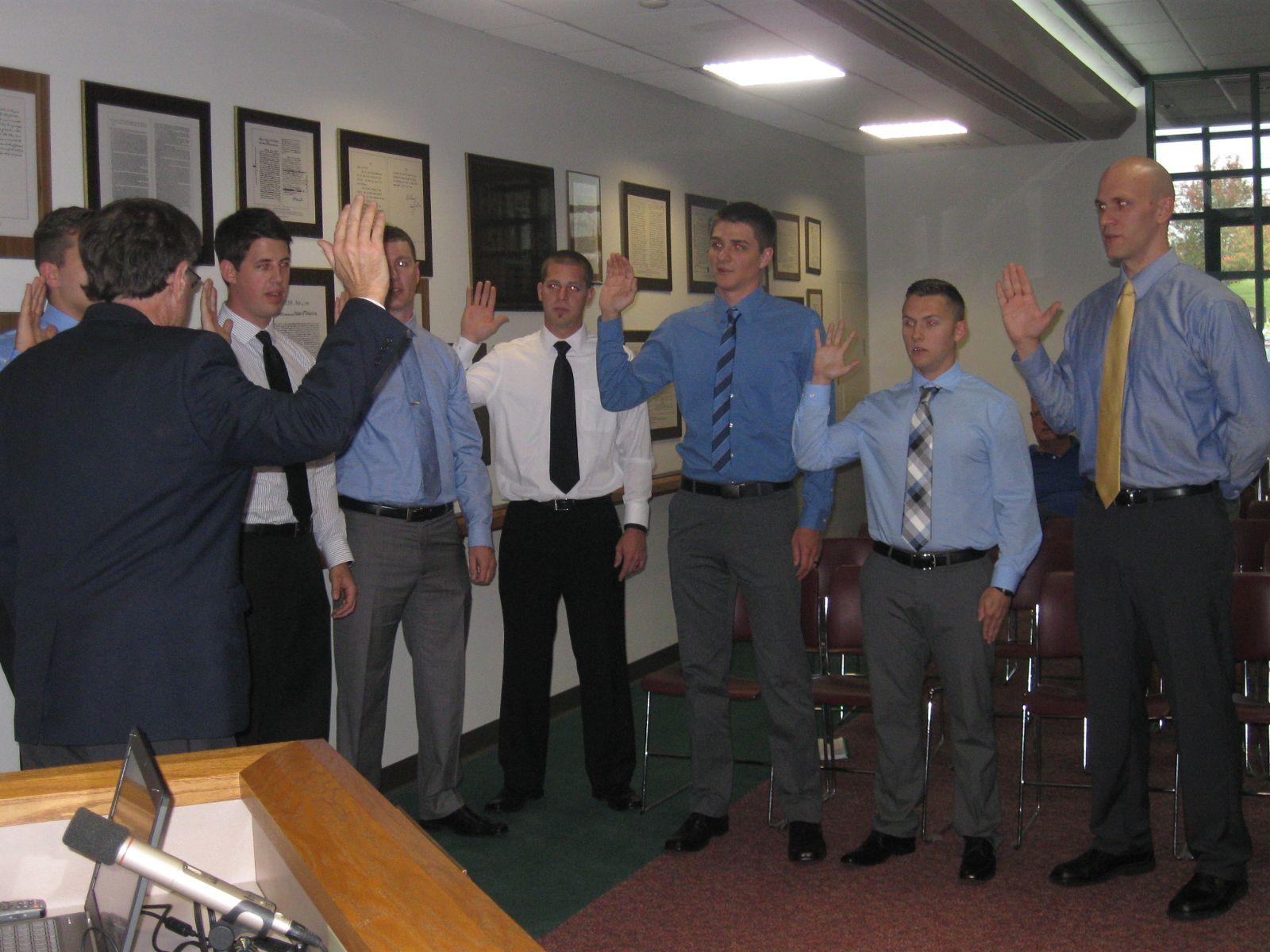 Image of Fiscal Officer Tom Straus swears in seven new part-time firefighters at the Green Township Board of Trustees Meeting